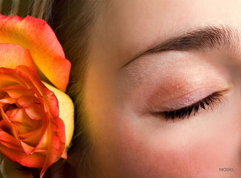 Woman with youthful, closed eye next to a orange flower. Facial rejuvenation concept.